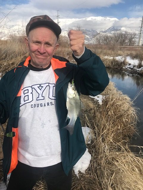 Kirk Rasmussen is holding a white bass caught on Utah Lake.